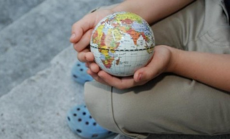 child holding globe - sustainability